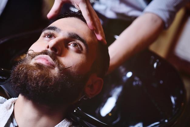 Fryzjer lub fryzjer myje głowę klienta