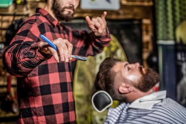 Fryzjer męski goli brodę. brodaty mężczyzna siedzi w fotelu w zakładzie fryzjerskim, podczas gdy fryzjer goli brodę niebezpieczną brzytwą. fryzjer golący brodatego mężczyznę w zakładzie fryzjerskim. zbliżenie.