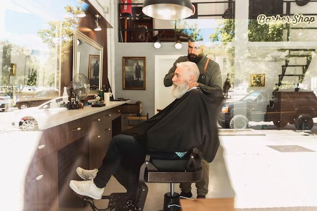Fryzjer męski robi ostrzyżeniu brodatego starzejącego się klienta w włosianym salonie