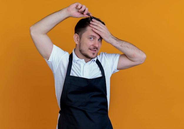 Fryzjer mężczyzna w fartuch czesanie włosy patrząc na kamery z uśmiechem na twarzy stojącej na pomarańczowym tle