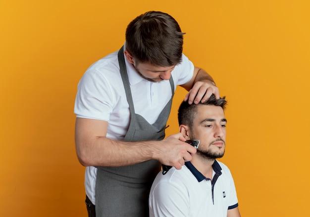 Fryzjer mężczyzna w fartuch do golenia brody z brodą trymer zadowolony klient na pomarańczowym tle