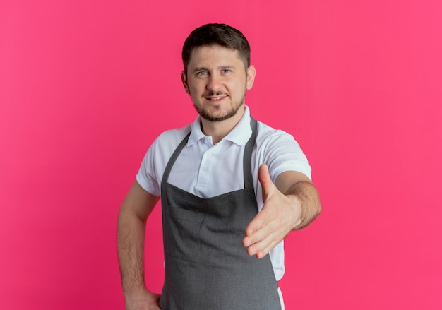 Fryzjer mężczyzna w fartuch patrząc na kamery oferujące powitanie strony uśmiechnięty przyjazny stojący na różowym tle