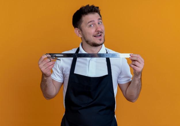 Fryzjer mężczyzna w fartuch pokazujący linijkę z uśmiechem na twarzy stojącej nad pomarańczową ścianą