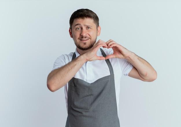 Fryzjer mężczyzna w fartuch robi gest serca palcami uśmiechnięty wesoło stojąc na białym tle