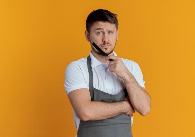 Fryzjer mężczyzna w fartuch trzymając grzebień lookign na aparat z poważną twarzą stojącą na pomarańczowym tle