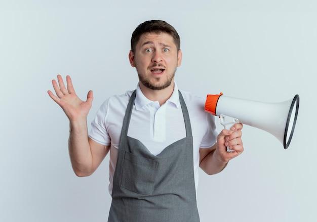 Fryzjer mężczyzna w fartuch trzymając megafon patrząc na kamery zdezorientowany stojący na białym tle