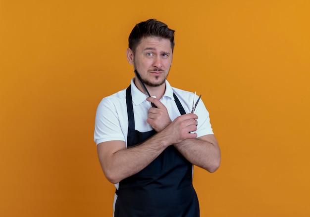 Fryzjer mężczyzna w fartuch trzymając nożyczki i grzebień patrząc na kamery z poważną twarzą stojącą na pomarańczowym tle