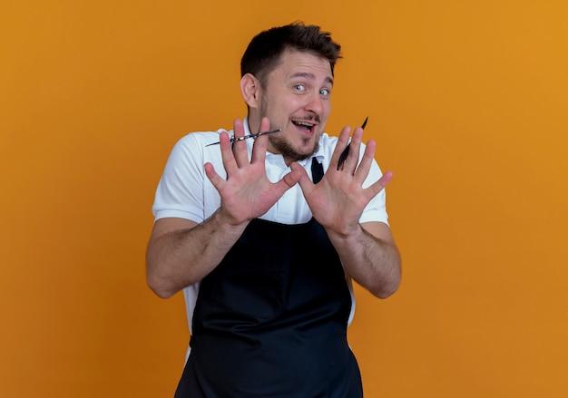 Fryzjer mężczyzna w fartuch, trzymając nożyczki i grzebień, robi gest stop z rękami stojącymi na pomarańczowym tle