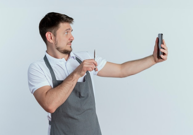 Fryzjer mężczyzna w fartuch trzymając nożyczki, robiąc sobie zdjęcie za pomocą smartfona stojącego na białej ścianie