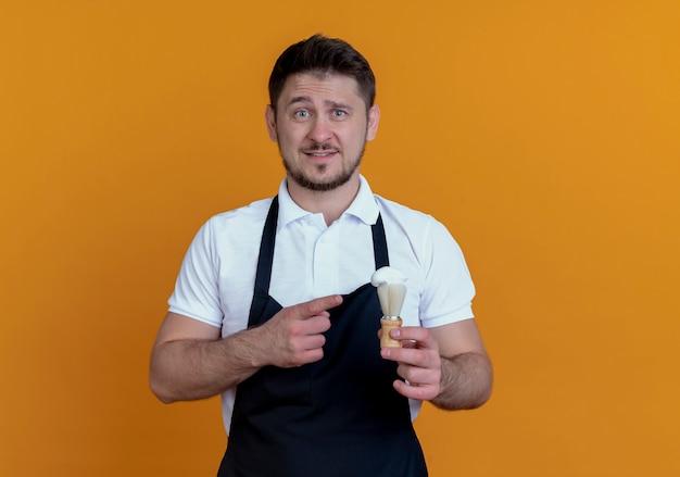 Fryzjer mężczyzna w fartuch trzymając pędzel do golenia wskazujący palcem z uśmiechem na twarzy stojącej nad pomarańczową ścianą