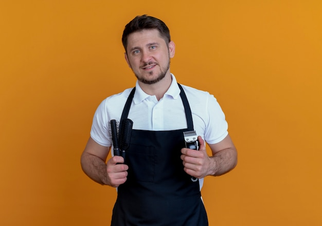 Fryzjer mężczyzna w fartuch trzymając pędzle i trymer do brody uśmiechnięty stojący nad pomarańczową ścianą