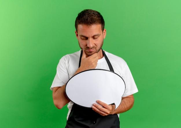 Fryzjer mężczyzna w fartuch trzymając pusty znak bańki mowy patrząc na to z zamyślonym wyrażeniem myśli stojącej nad zieloną ścianą