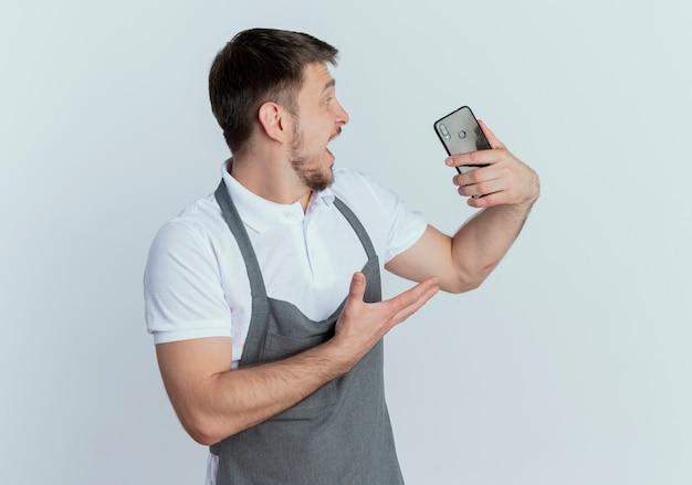 Fryzjer mężczyzna w fartuch trzymając smartfon patrząc na to podekscytowany stojąc nad białą ścianą