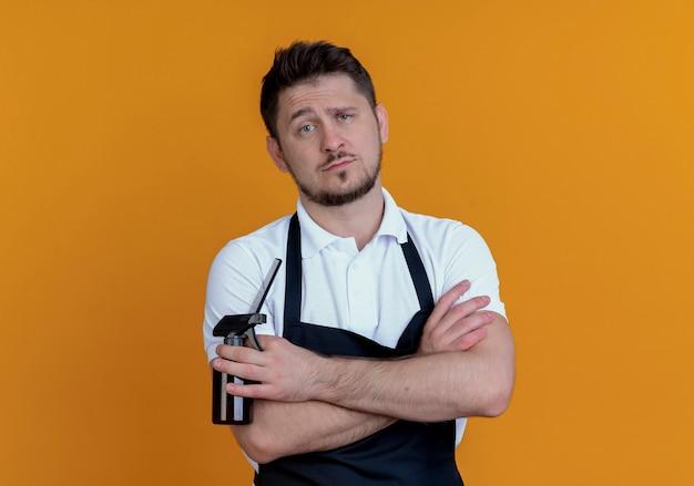 Fryzjer mężczyzna w fartuch trzymając spray i grzebień patrząc na kamery poważną twarz stojącą na pomarańczowym tle