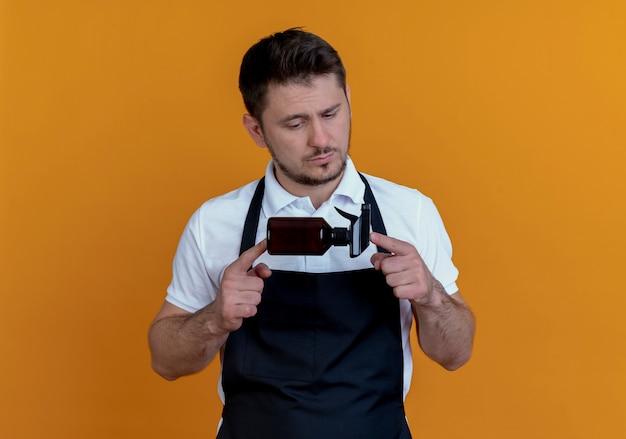 Fryzjer mężczyzna w fartuch trzymając spray patrząc na to z poważną twarzą stojącą na pomarańczowym tle