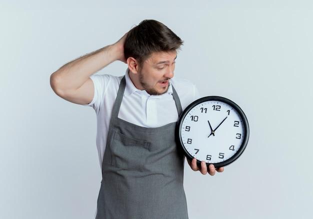 Fryzjer mężczyzna w fartuch trzymając zegar ścienny patrząc na to zdezorientowany ręką na głowie stojącego nad białą ścianą