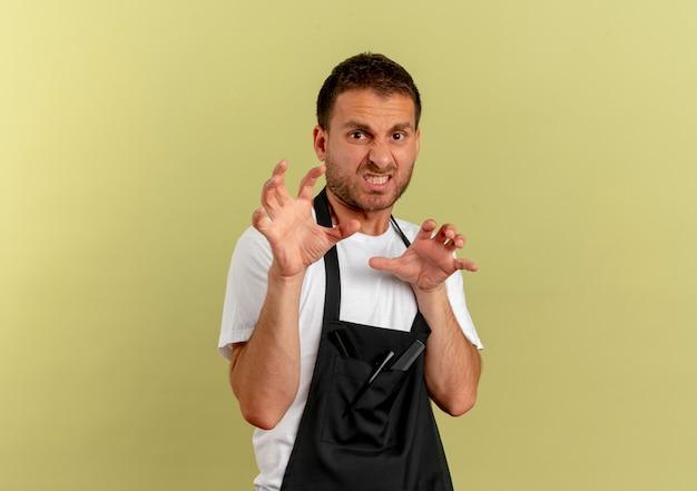 Fryzjer mężczyzna w fartuchu czyniąc gest obrony rękami z obrzydzonym wyrazem stojącym nad jasną ścianą