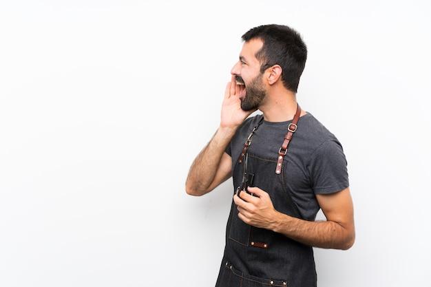 Fryzjer mężczyzna w fartuchu krzyczy z szeroko otwartymi ustami do boku