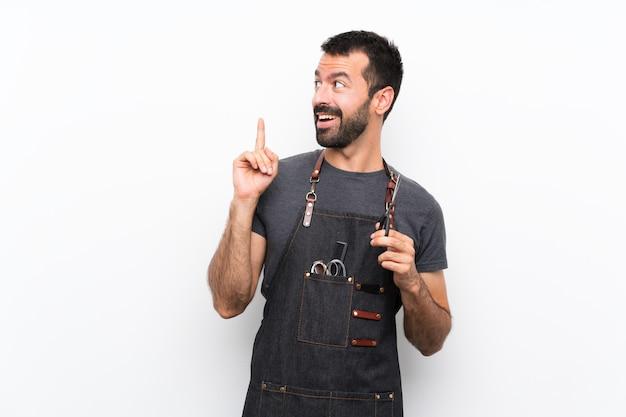 Fryzjer mężczyzna w fartuchu myśli pomysł skierowany palcem w górę