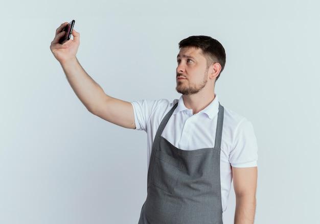 Fryzjer mężczyzna w fartuchu, patrząc na ekran swojego smartfona, robiąc zdjęcie siebie stojącego na białym tle