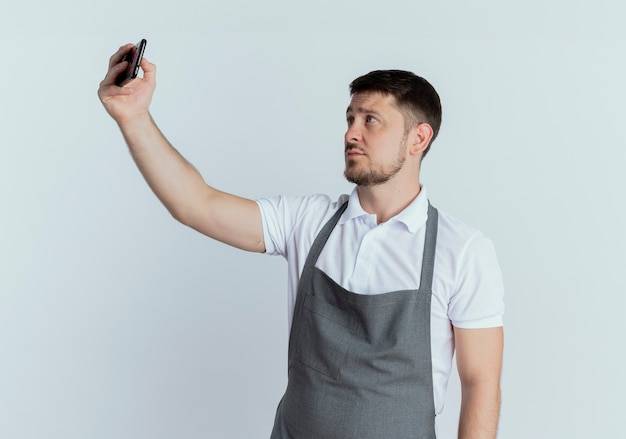 Fryzjer mężczyzna w fartuchu, patrząc na ekran swojego smartfona, robiąc zdjęcie siebie stojącego nad białą ścianą