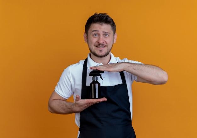Fryzjer mężczyzna w fartuchu pokazano spray patrząc na to z uśmiechem na twarzy stojącej na pomarańczowym tle