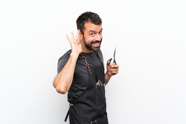 Fryzjer mężczyzna w fartuchu, słuchając czegoś, kładąc rękę na uchu