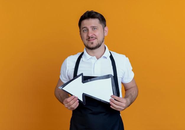 Fryzjer mężczyzna w fartuchu trzymając białą strzałkę z uśmiechem na twarzy stojącej nad pomarańczową ścianą
