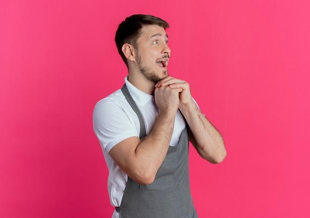 Fryzjer mężczyzna w fartuchu, trzymając się za ręce razem szczęśliwy i podekscytowany, patrząc na bok stojąc na różowym tle