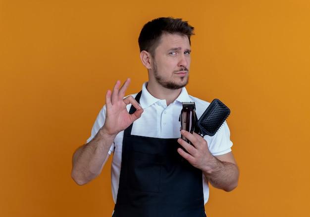 Fryzjer mężczyzna w fartuchu, trzymając szczotkę do włosów i trymer do brody, pokazując znak ok, patrząc pewnie stojąc nad pomarańczową ścianą