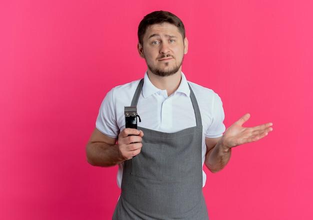 Fryzjer mężczyzna w fartuchu trzymając trymer do brody patrząc na aparat zdezorientowany i niezadowolony, stojąc na różowym tle
