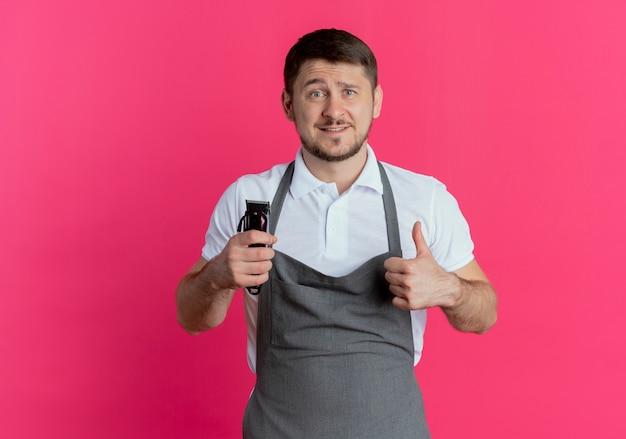 Fryzjer mężczyzna w fartuchu trzymając trymer do brody patrząc na kamery pokazujące kciuki do góry uśmiechnięty stojący na różowym tle