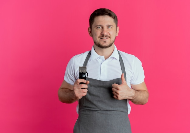 Fryzjer mężczyzna w fartuchu trzymając trymer do brody pokazując kciuki do góry uśmiechnięty patrząc na aparat stojący na różowym tle