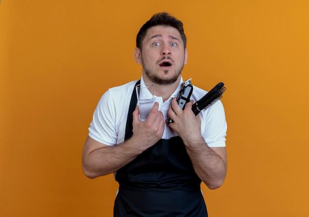 Fryzjer mężczyzna w fartuchu, trzymając trymer do brody, szczotka do włosów i szklankę wody patrząc na aparat zdezorientowany stojąc na pomarańczowym tle