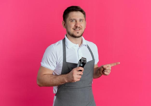 Fryzjer mężczyzna w fartuchu trzymając trymer do brody wskazując palcem w bok uśmiechnięty stojący na różowym tle