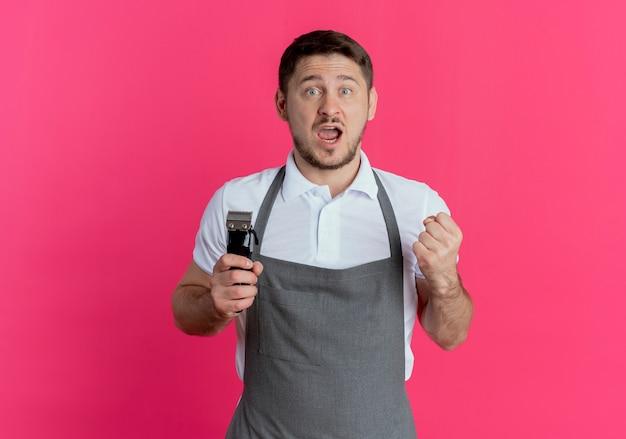 Fryzjer mężczyzna w fartuchu trzymający trymer do brody zaciskający pięść szczęśliwy i podekscytowany stojący nad różową ścianą