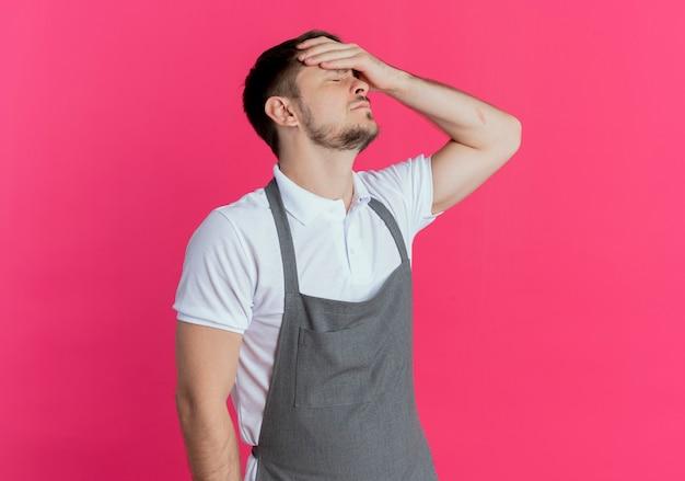 Fryzjer mężczyzna w fartuchu wyglądający na zmęczonego i znudzonego ręką nad głową stojącego na różowym tle