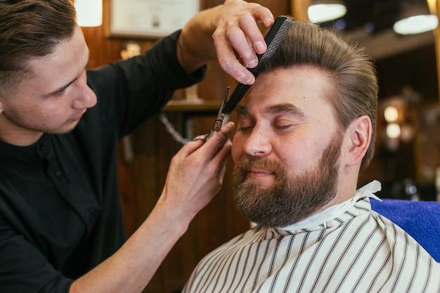 Fryzjer, mężczyzna z fryzjerem na brodę. piękne włosy i pielęgnacja, salon fryzjerski dla mężczyzn