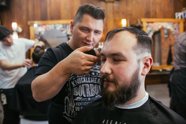 Fryzjer, mężczyzna z fryzjerem na brodę. profesjonalna fryzura, retro fryzura i stylizacja
