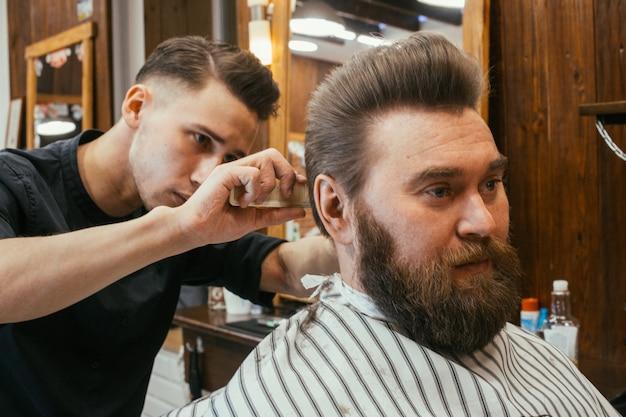 Fryzjer, mężczyzna z fryzjerem obciętym brodą. piękne włosy i pielęgnacja, salon fryzjerski dla mężczyzn. profesjonalna fryzura, fryzura i stylizacja retro. obsługa klienta. rosja, swierdłowsk, 12 lutego 2018 r.