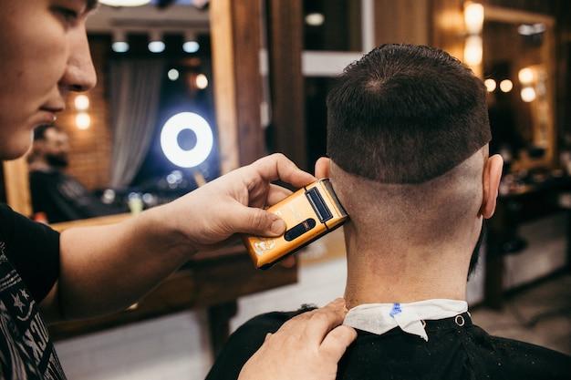 Fryzjer, mężczyzna z fryzjerem obciętym brodą. profesjonalna fryzura, fryzura i stylizacja retro. piękne włosy i pielęgnacja, salon fryzjerski dla mężczyzn. obsługa klienta. rosja, swierdłowsk, 12 lutego 2018 r.