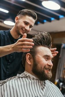 Fryzjer, mężczyzna z fryzjerem ściętym na brodzie. piękne włosy i pielęgnacja, salon fryzjerski dla mężczyzn. profesjonalna fryzura, fryzura retro i stylizacja