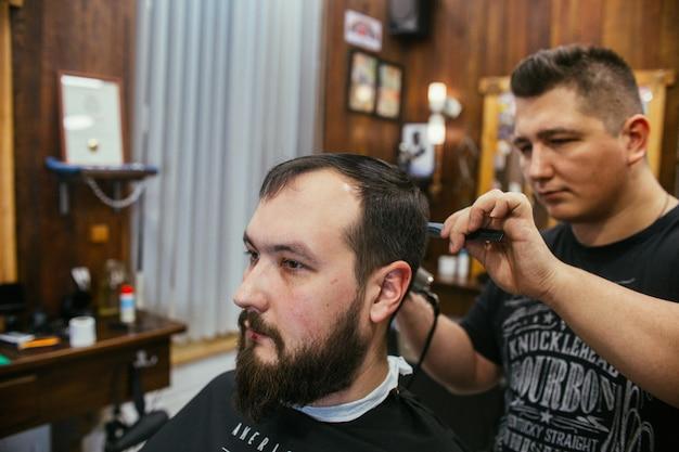 Fryzjer, mężczyzna z fryzjerem z ciętą brodą