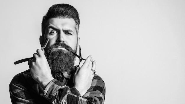 Fryzjer mężczyzna z prostą brzytwą i nożyczkami.