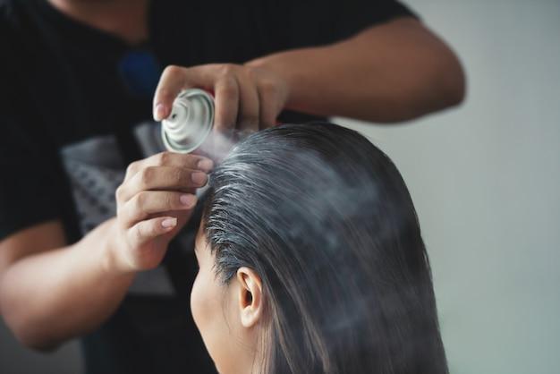 Fryzjer mocujący fryzurę z lokami kobiety używającej lakieru do włosów w salonie piękności