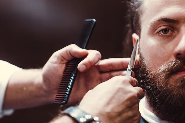 Fryzjer. model brodaty mężczyzna i fryzjer z nożyczkami.