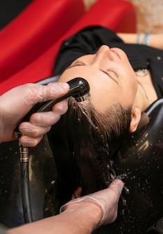 Fryzjer myjący kobiecie włosy