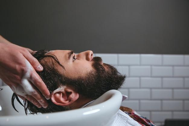 Fryzjer myjący włosy klienta w salonie fryzjerskim