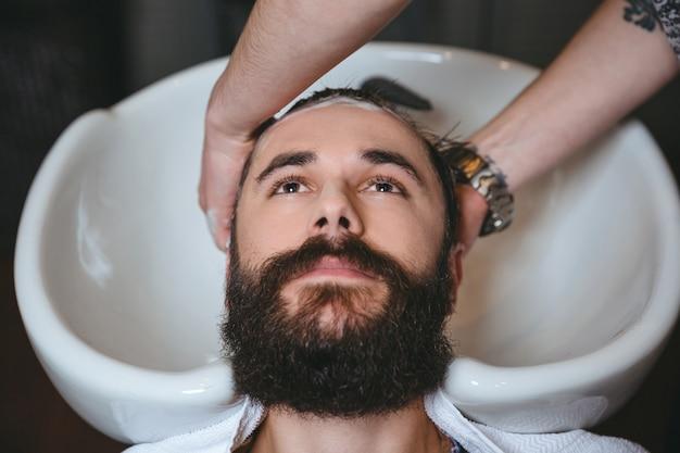 Fryzjer myje głowę młodego atrakcyjnego mężczyzny z brodą w zakładzie fryzjerskim