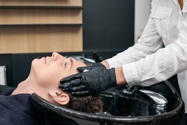 Fryzjer myje włosy klienta w zlewie pięknego salonu.